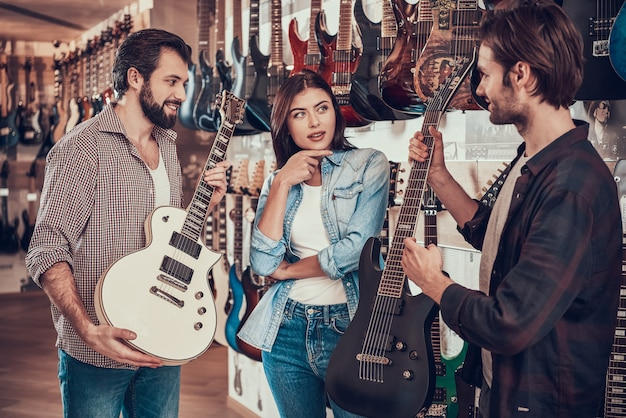 Couple buying new electric guitar in music store.