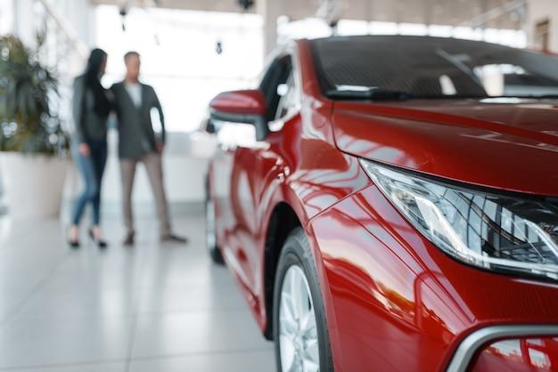 쇼 룸에서 새 빨간 자동차를 구입하는 커플.