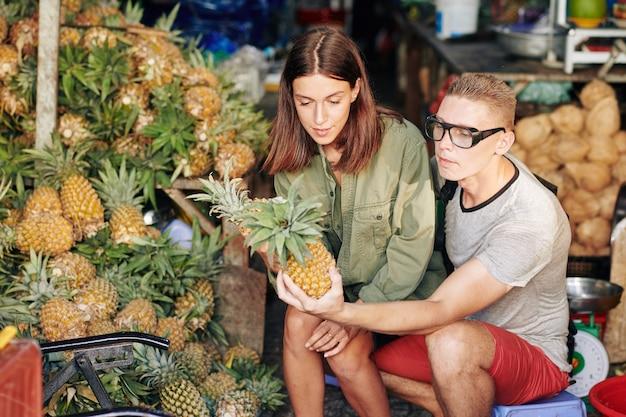 Пара, покупающая ананасы