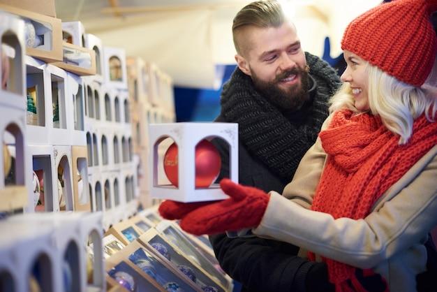 クリスマスマーケットで最大のクリスマスボールを買うカップル