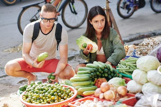Пара, покупающая овощи на рынке