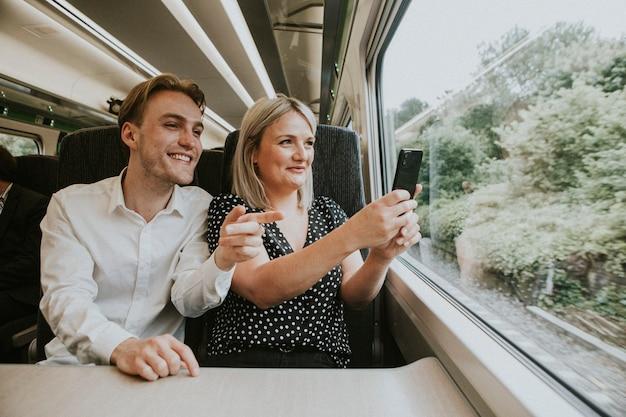 風景写真を撮る電車の窓際のカップル