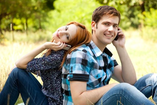 夏の屋外で携帯電話で呼び出すカップル。