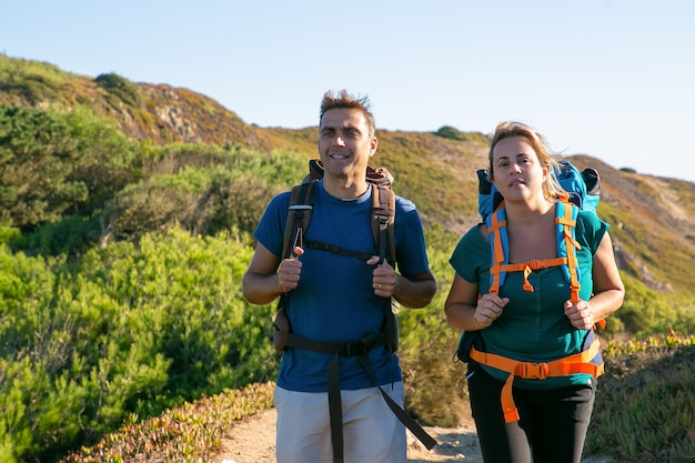 Couple of campers hiking outdoors, walking on countryside path, looking away. front view. nature and recreation concept