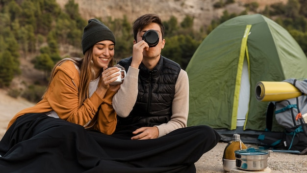 Couple camping and drinking tea together
