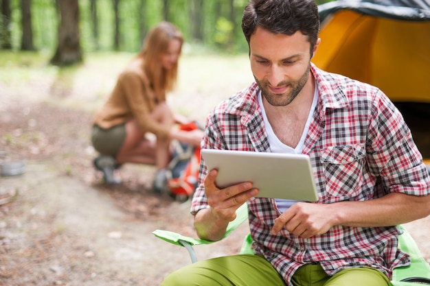 Couple camping in the forest. man using a digital tablet