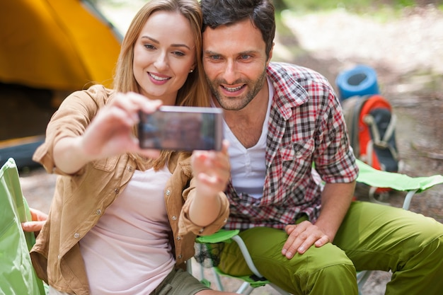 Couple camping in the forest and taking a photo