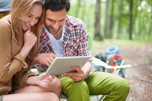Пара кемпинг в лесу. пара с помощью цифрового планшета в лесу