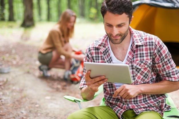 숲에서 캠핑하는 커플. 디지털 태블릿을 사용하는 사람