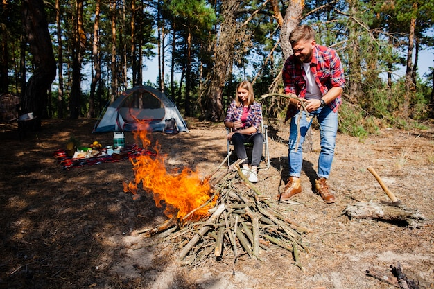 Couple camping making fire in woods