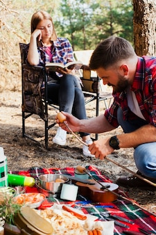 Couple camping and preparing food for meal