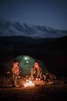 Couple in camping with campfire at night in mountains