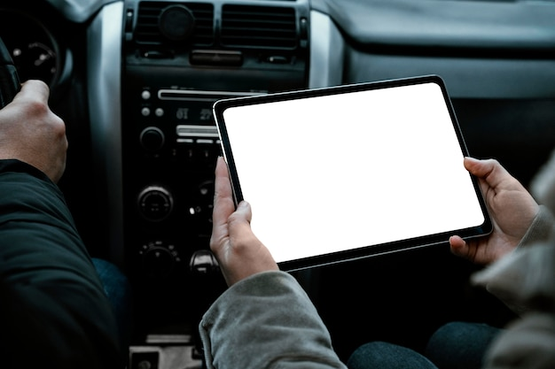 Couple in the car consulting tablet while on a road trip