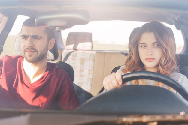 Couple in car on road trip: concentrated experienced female driver sits at wheel and her husband