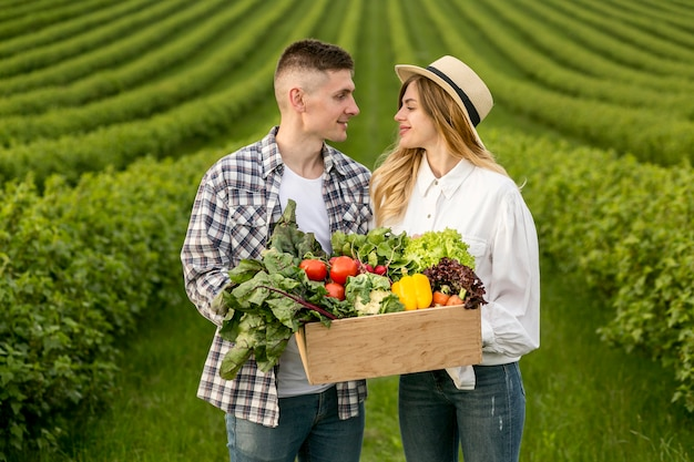 Couple carrying basket vegetables