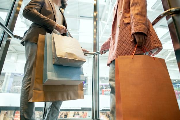 買い物の後に紙袋の束を運ぶカップル