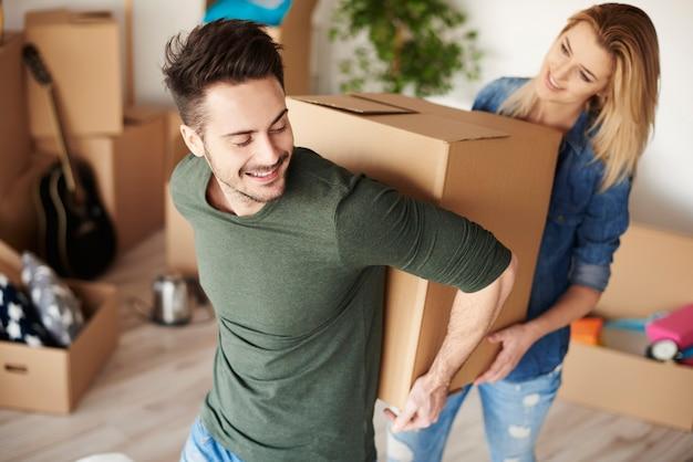 Coppia che trasporta insieme pesanti scatoloni per trasloco