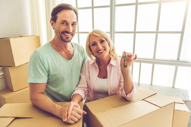 Couple in casual clothes is leaning on the boxes.