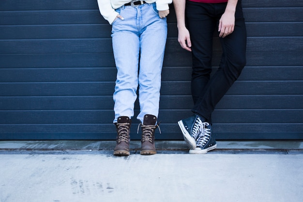 Couple in casual clothes standing against blue wall