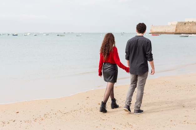 Couple in casual clothes walking on sea shore