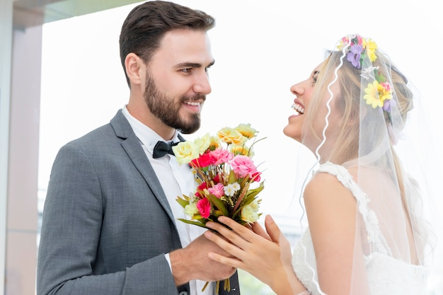 Couple of caucasian, groom give present bride in wedding studio.