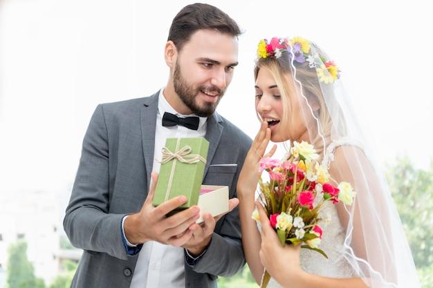 Couple of caucasian, groom give present bride in wedding studio.