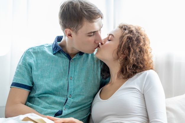 Couple caucasian kissing together while lying in bed.