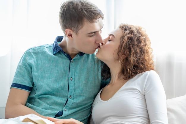 Пара кавказских поцелуи вместе лежа в постели.