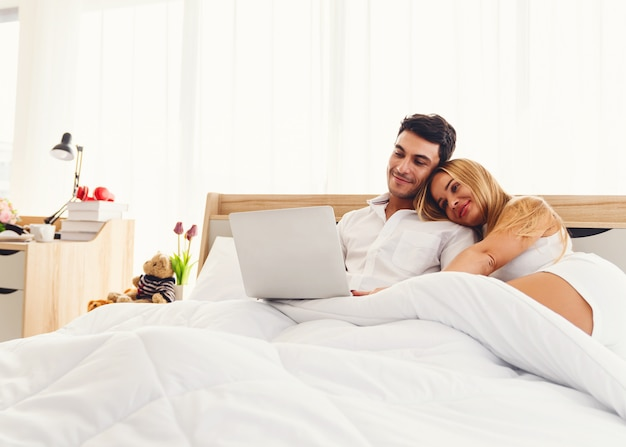 Couple caucasian lover smiling enjoy using laptop computer together on bed early morning