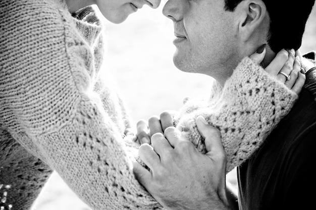 Couple of caucasian model man and woman hug and love with passion taking themselves and stay close lips to lips. little smile and face together in a true relationship image black and white concept