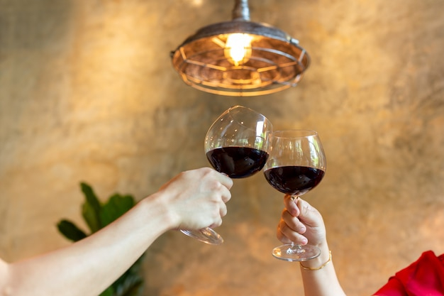 Couple celebrate toasting glasses of red wine in restaurant.