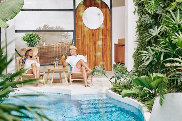 スパホテルで結婚記念日を祝うカップルは、プールサイドで日光浴をしたり、カクテルを飲んだり、話したりしています。