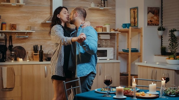 お祝いの夕食の間に、台所に座って踊って祝うカップル。愛のカップルが家で一緒に食事をしたり、食事を楽しんだり、笑顔で楽しんだり、結婚記念日を祝ったりして幸せです。