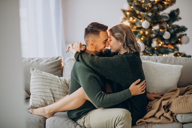 Couple celebrating christmas together at home, kissing next to christmas tree