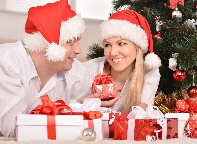 家で新年を祝うカップルが贈り物でカーペットの上に横たわっている
