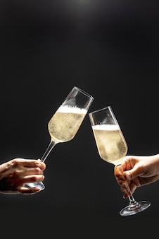 Couple celebrating with champagne on dark background