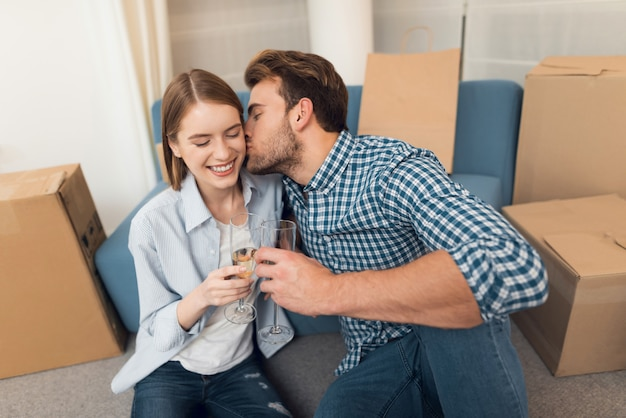 Couple celebrating with champagne moving to new apartment.