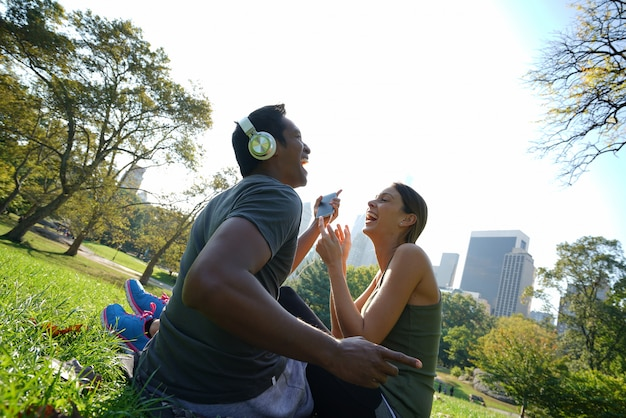 Couple at central park listening to music on smartphone