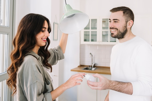 Couple changing bulb at home