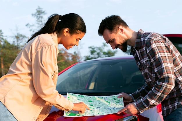 車の新しい目的地の地図をチェックするカップル