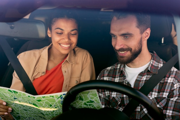 新しい目的地のために車の中で地図をチェックしているカップル