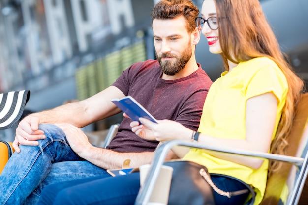 Пара проверяет паспорта, сидя в зале ожидания аэропорта во время летних каникул