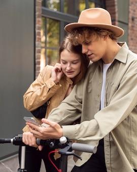 Пара проверяет смартфон на электросамокатах