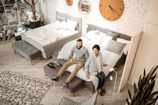 Пара проверяет мягкость. смеющаяся позитивная пара наслаждается процессом покупок в мебельном магазине, сидя на кровати размера «king-size»