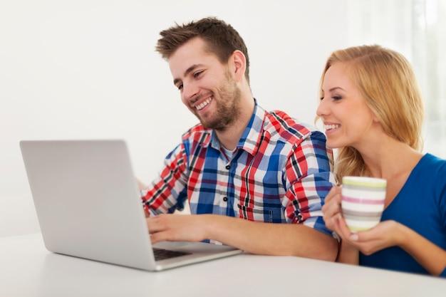 自宅のコンピューターで何かをチェックするカップル