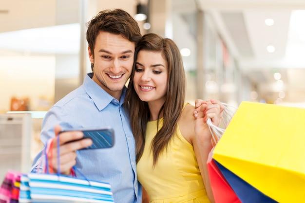 Пара что-то проверяет по мобильному телефону во время покупок