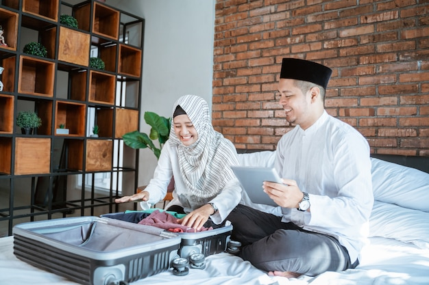 Couple checklist their stuff on suitcase