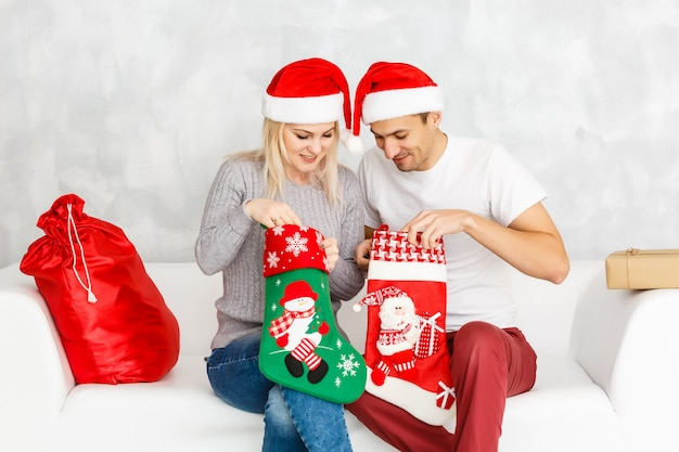 Couple cheerful face check out gift in christmas sock.
