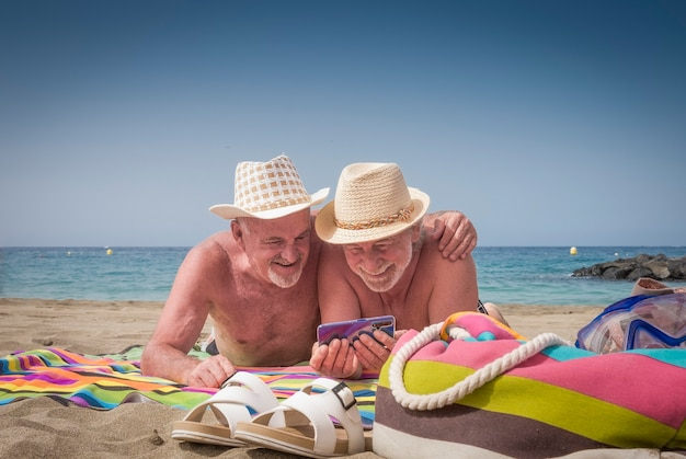 Couple of cheerful senior brothers in holidays at the beach having fun together with smart phone, straw hats and horizon over water - concept of active playful elderly during vacations