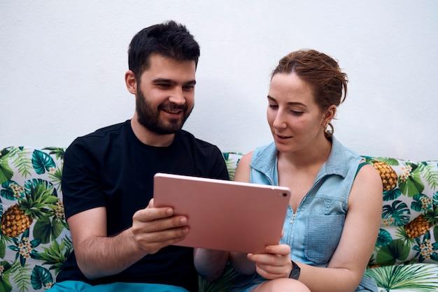 태블릿을 사용 하여 휴가 목적지를 선택하는 커플